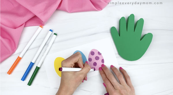 hand decorating paper easter eggs with markers