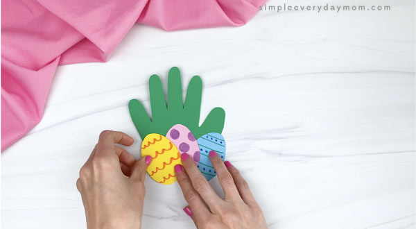 hand gluing paper Easter eggs to handprint Easter card craft