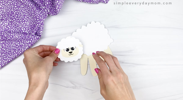 hand gluing head onto handprint sheep craft