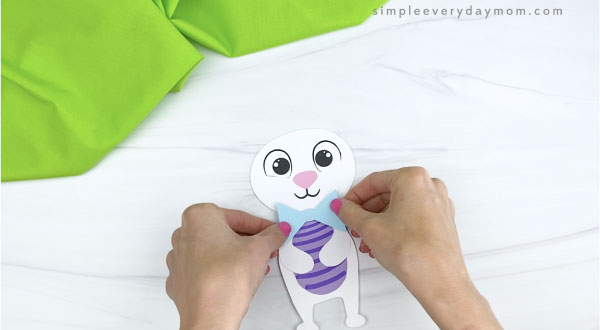 hands gluing bowtie onto paper Easter bunny craft