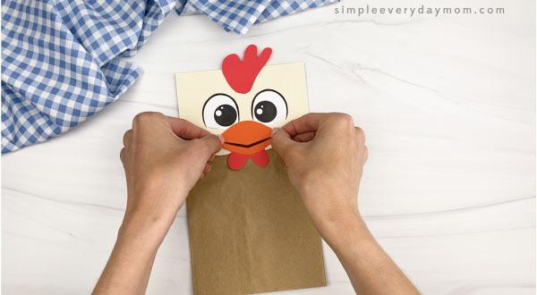 hand gluing beak to paper bag chicken craft