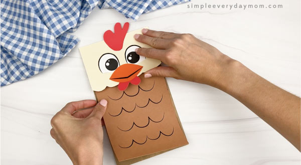 hand gluing body to paper bag chicken craft