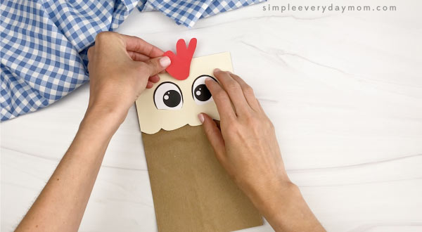hand gluing comb to paper bag chicken craft