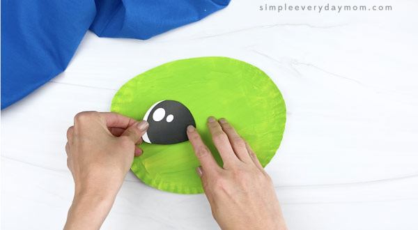 hand gluing eye onto paper plate baby yoda craft