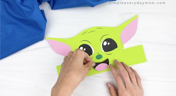 hands gluing mouth to Baby Yoda headband craft