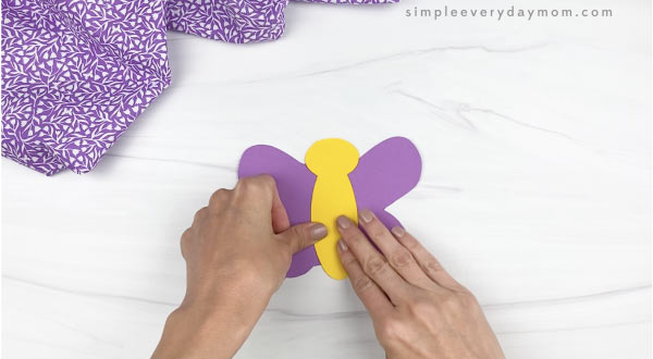 hand gluing body to butterfly stick puppet