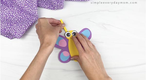hand gluing antenna to butterfly stick puppet