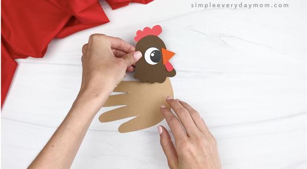 hand gluing head to handprint chicken craft