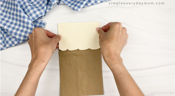 hand gluing head to paper bag chicken craft