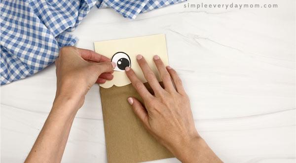hand gluing eyes to paper bag chicken craft