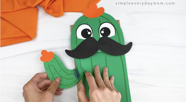 hand gluing arms to paper bag cactus craft