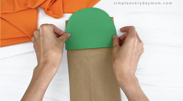 hand gluing head to paper bag cactus craft