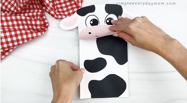 hand gluing body to paper bag cow craft