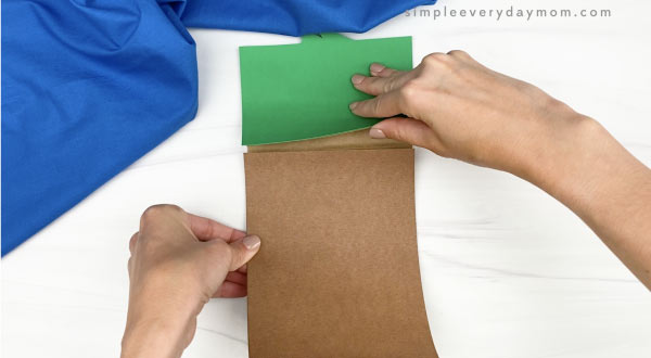 hand gluing body to duck paper bag craft