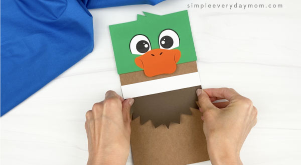hand gluing feathers to duck paper bag craft