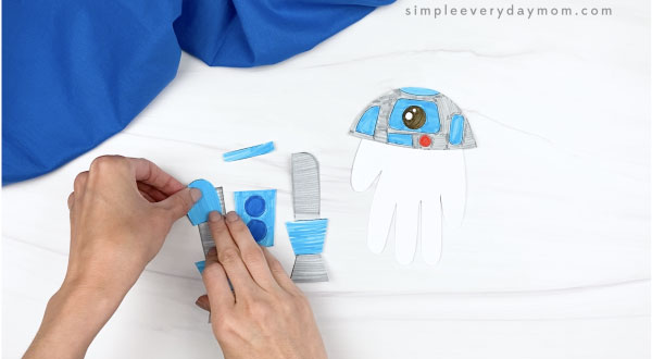 hand gluing handprint r2d2 craft pieces together