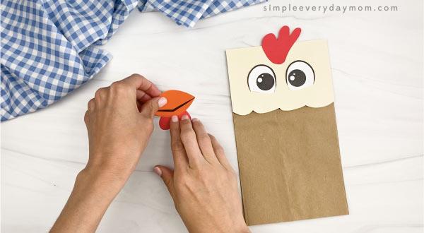 hand gluing wattle to beak of paper bag chicken craft