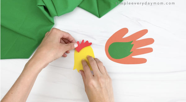 hands gluing comb to handprint rooster craft
