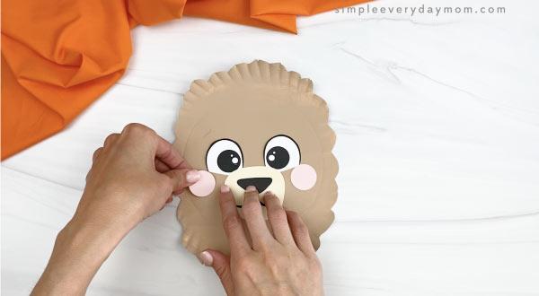 hand gluing cheeks onto paper plate llama craft
