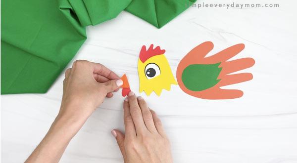 hands gluing wattle to handprint rooster beak