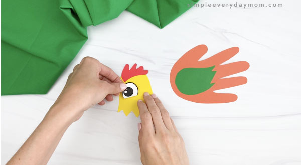 hands gluing eye to handprint rooster craft