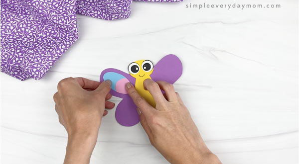 hand gluing wing decorations to butterfly stick puppet