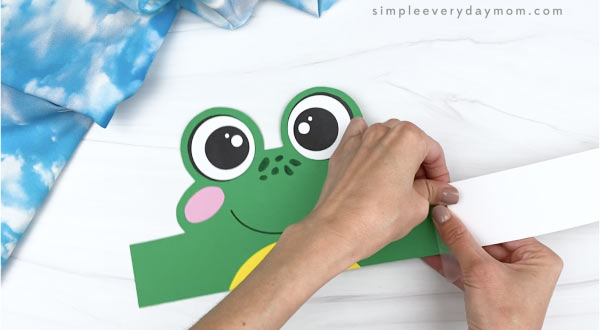 hands taping extenders to frog headband craft