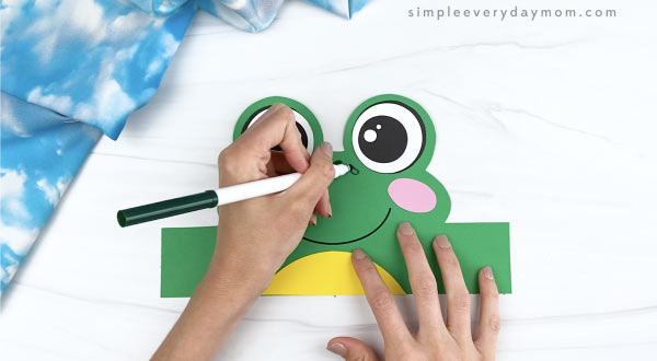 hand drawing spots on frog headband craft