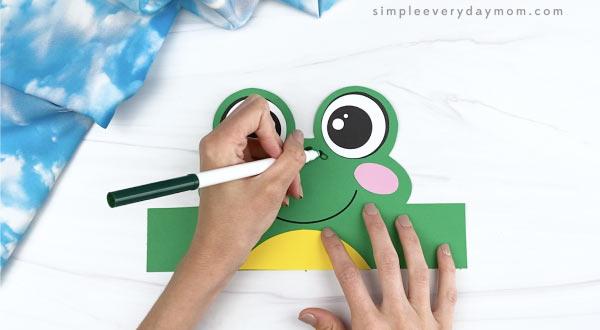 hand drawing spots on frog headband craft
