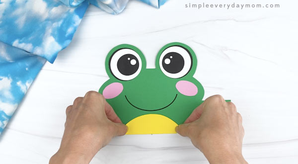 hand gluing belly to frog headband craft
