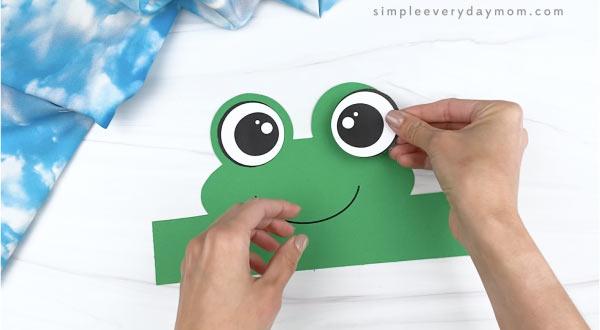 hand gluing eye to frog headband craft