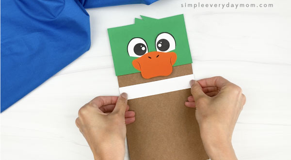 hand gluing neck strip to duck paper bag craft
