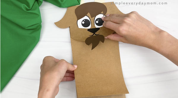 hand gluing body to paper bag goat craft