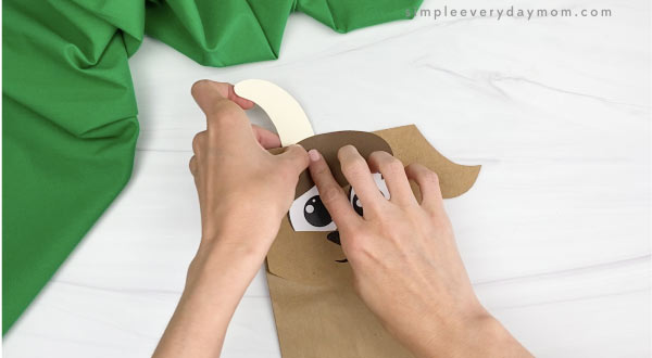 hand gluing horns to paper bag goat craft