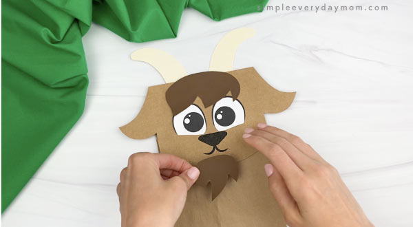 hand gluing goatee to paper bag goat craft
