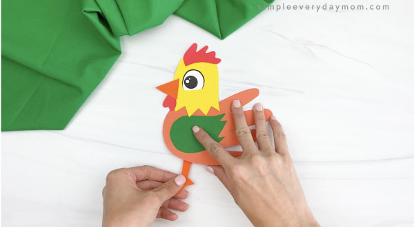 hand gluing legs to handprint rooster craft