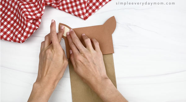 hand gluing inner ear to paper bag horse craft