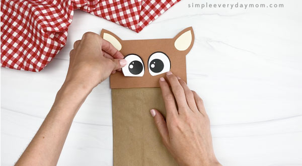 hand gluing eye to paper bag horse craft