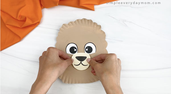 hand gluing nose/mouth onto paper plate llama craft