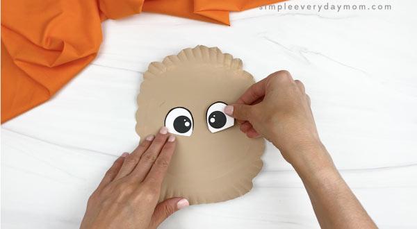 hand gluing eyes onto paper plate llama craft