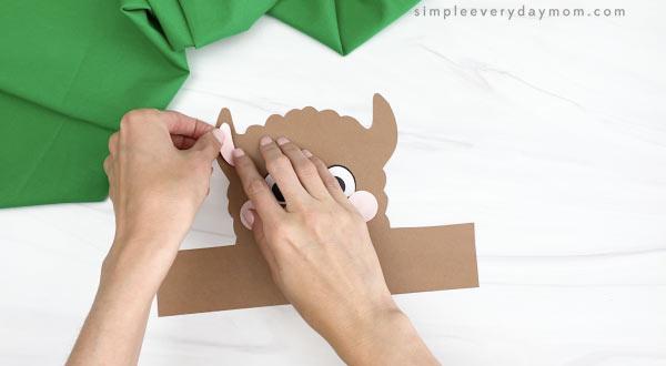 hand gluing inner ear to llama headband craft