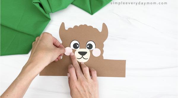 hand gluing cheek to llama headband craft