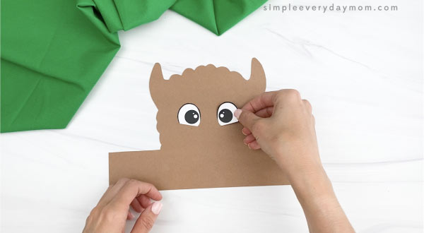 hand gluing eye to llama headband craft