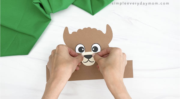 hand gluing nose and mouth to llama headband craft