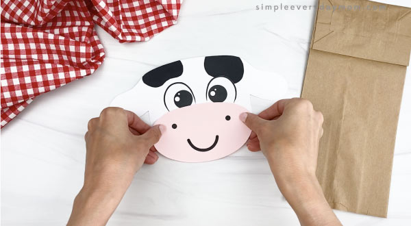 hand gluing mouth to paper bag cow craft