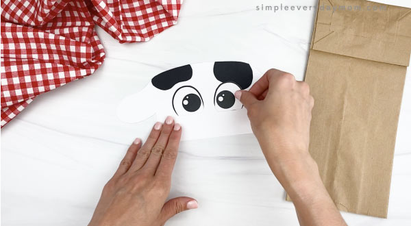hand gluing eyes to paper bag cow craft