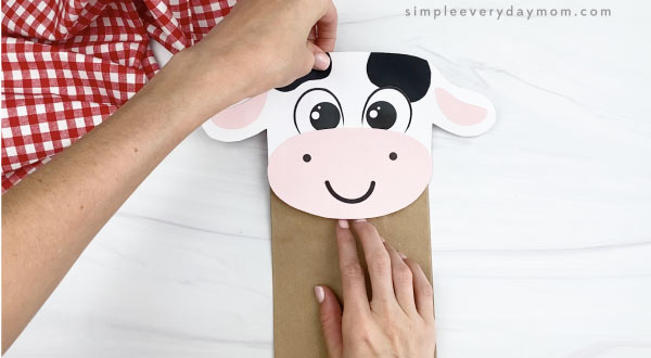 hand gluing head to paper bag cow craft