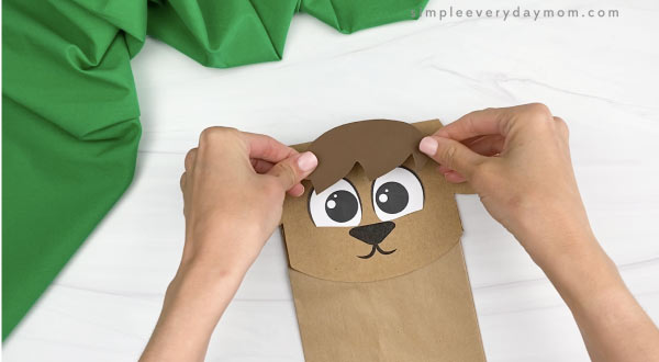 hand gluing hair to paper bag goat craft