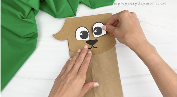 hand gluing eye to paper bag goat craft