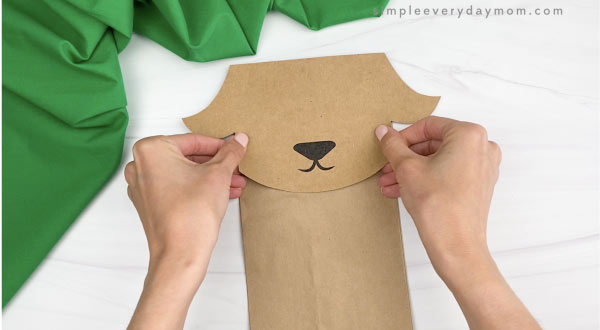 hand gluing head to paper bag goat craft